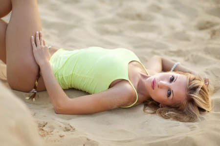 Young blond female lying on tropical beach with sand in yellow top photo