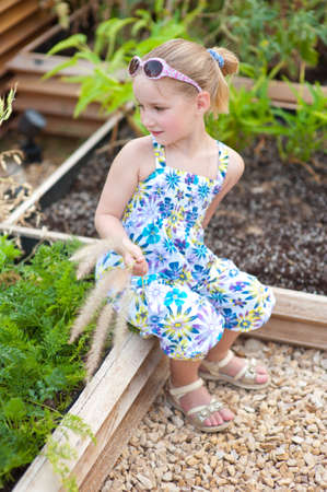 Toddler blond girl sitting in garden with vegetables in sunglasses photo