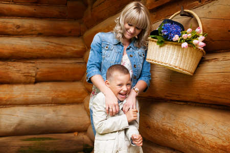Happy blond mother playing with her toddler son near country house and laughing photo