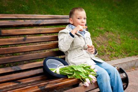 Happy toddler boy sitting on bench in green park eating colorful candy photo