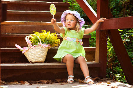 Beautiful toddler girl in hat eating lollipop in summer park Stock Photo