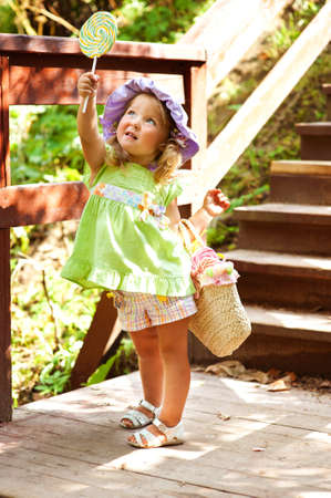 lollipops: Beautiful toddler girl in hat eating lollipop in summer park Stock Photo