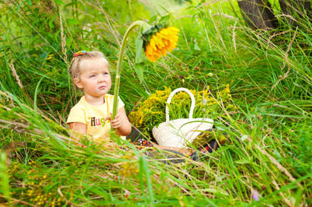 Adorable blond girl sitting in grass with sunflowers and smiling photo