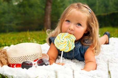 Funny blond toddler girl with lollipop lying on white plaid photo