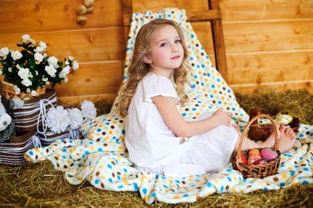 Adorable european girl in hay celebrates easter