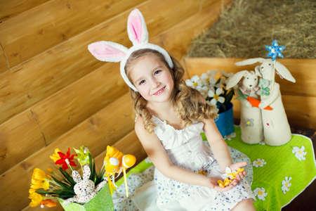Happy girl in fancy bunny ears celebrating easter in country house