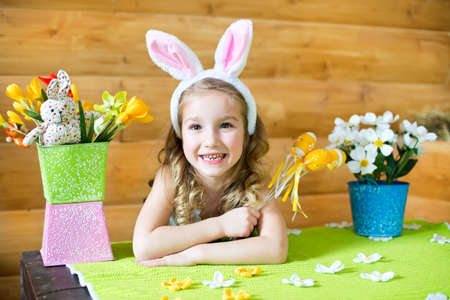 Happy girl in fancy bunny ears celebrating easter in country house photo