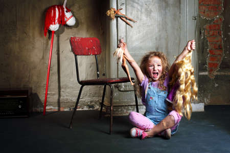 dirty blond: Dirty blond girl with dolls in basement screams and protests Stock Photo