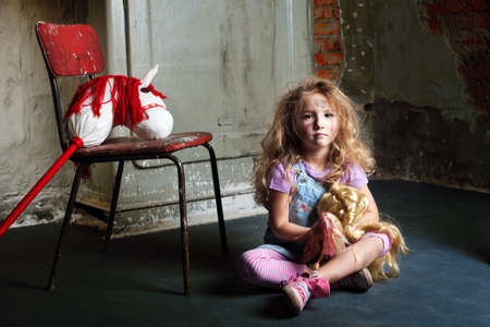 dirty blond: Dirty blond girl with dolls in basement sitting on floor
