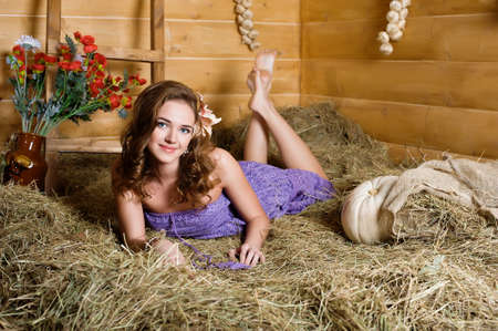 hayloft: Pretty young woman lies in hay and smiles Stock Photo