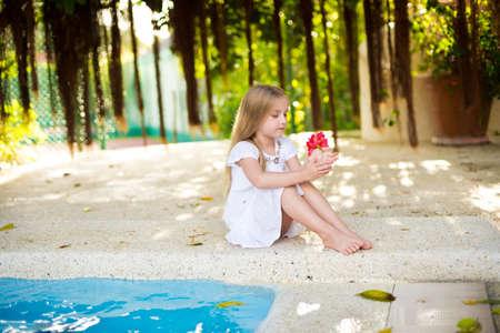 Adorable european toddler girl in tropical garden near swimming pool photo