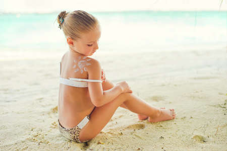 child swimsuit: Adorable toddler girl in bikini with picture of sun made from cream on shoulder sitting on beach Stock Photo
