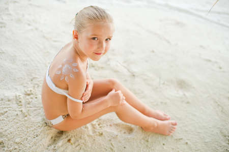 little girl swimsuit: Adorable toddler girl in bikini with picture of sun made from cream on shoulder sitting on beach Stock Photo