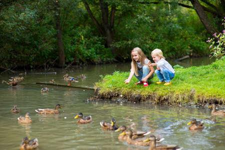 Two cute sisters on river shore feeding ducks Stock Photo