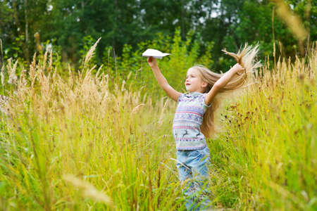 paper airplane: Cute toddler european girl in autumn windy field playing with paper airplane