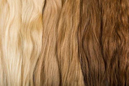 faux: Ciocche di capelli del faux per la bellezza salolon diversi colori e la struttura Bionda, rossa e bruna su sfondo grigio