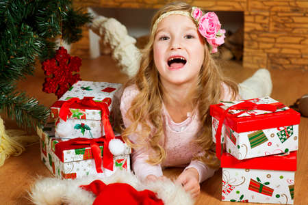 gaily: Happy european girl with long blond curly hair and flower on it lies under Christmas tree with her presents and screams gaily