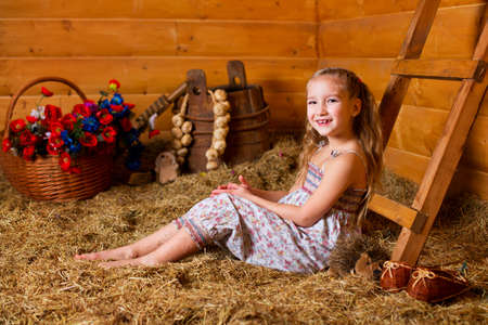 One beautiful blond european girl sitting on hay in wooden country house and playing  Colorful flowers in basket behind  photo