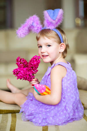Happy funny little girl with colorful pink flowers and fancy bunny ears on head celebrates easter  Toy han in hands