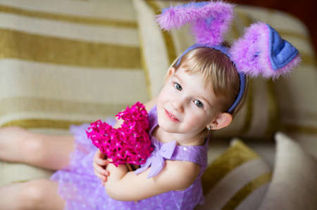 Happy funny little girl with colorful pink flowers and fancy bunny ears on head celebrates easter  Toy han in hands  photo