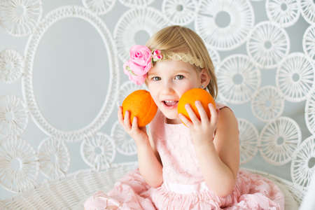 loves: Happy child girl with pink rose flower in blond hair sitting on lace chair and holding fresh oranges. She loves fruit and ready to eat it. Stock Photo