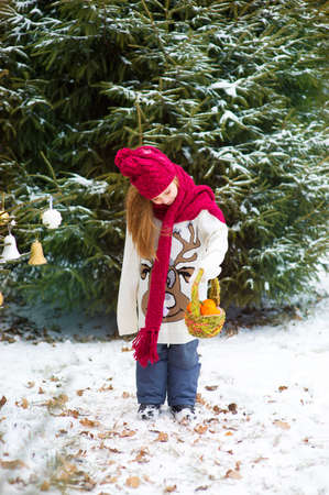 Beautiful toddler european child girl in winter forest with snow on trees celebrates Christmass and new year with basquet of mandarins in hands photo
