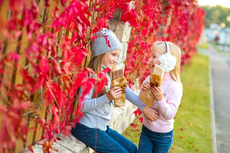 autumn garden: Two emotional cute sister girls sitting in colorful autumn garden, having fun and eating white and brown chocolate