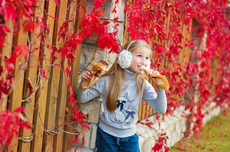 autumn garden: Beautiful blond toddler girl eating chocolate in colorful red leafs autumn garden Stock Photo