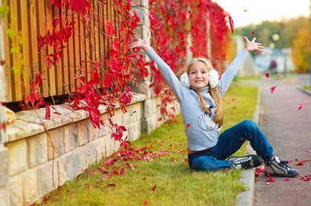 niñas bonitas: Hermosa niña niño Rubio caída de hojas de color rojo en el aire sentado en la hierba en el jardín colorido del otoño