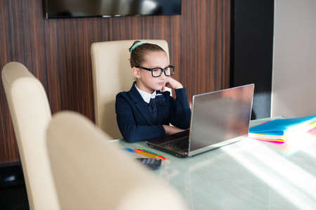 important: Beautiful toddler smart school girl in glasses sitting at table with laptop doing her home work
