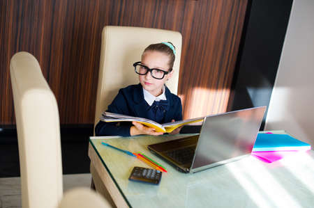internet school: Beautiful toddler smart school girl in glasses sitting at table with laptop doing her home work