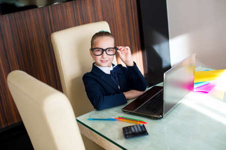 school exam: Beautiful toddler smart school girl in glasses sitting at table with laptop doing her home work