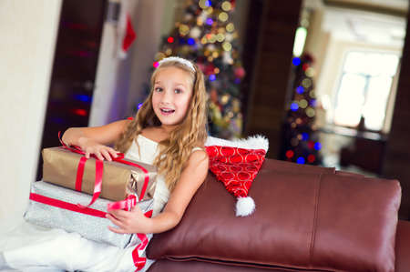 christmas present: Happy smiling toddler child girl happy to get her Christmas presents and make wish on New Year Eve, xmas tree on background