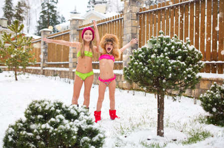 Two brave sisters stay outdoors under snow fall in bikini having extreme fun and tempering body