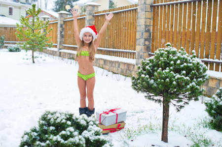 country girls: Brave child girl in bikini stay under snow fall in Santa Hat ready to celebrate Christmas outside Stock Photo