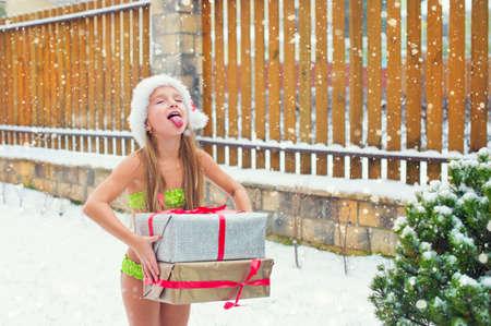 maillot de bain fille: Brave fille enfant dans séjour de bikini sous chute de neige à Santa Hat prêt à célébrer Noël à l'extérieur Banque d'images