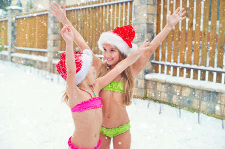 Two brave sisters stay outdoors under snow fall in bikini having extreme fun and tempering body in Santa Christmas hats