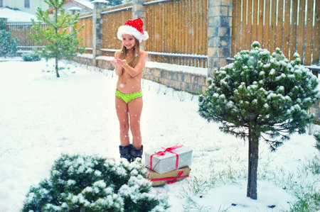 Brave child girl in bikini stay under snow fall in Santa Hat ready to celebrate Christmas outside Stock Photo