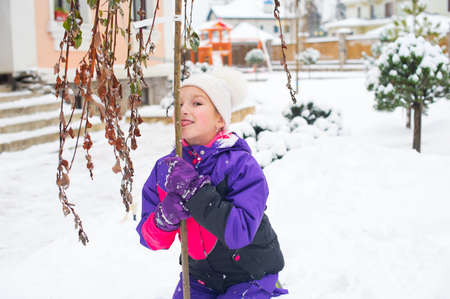 winter weather: Little girl in colorful suit lick tree with her tongue in cold winter weather Stock Photo