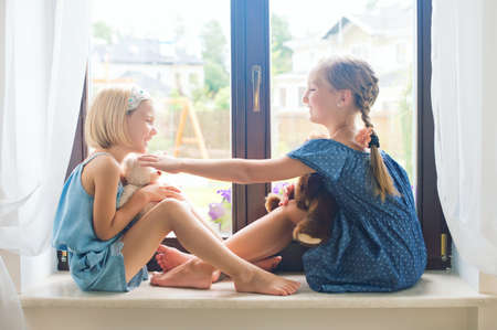 Two cute european toddler girls sitting on sill near window at home playing teddy bears happy and funny. Colorful back yard at background Imagens