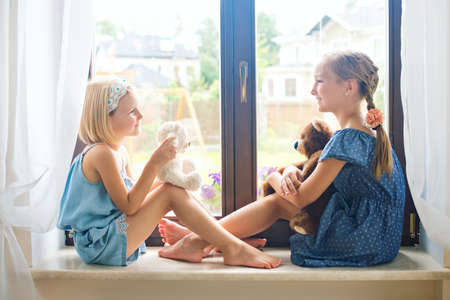 Two cute european toddler girls sitting near window at home playing teddy bears happy and funny. Colorful back yard at background Stock Photo