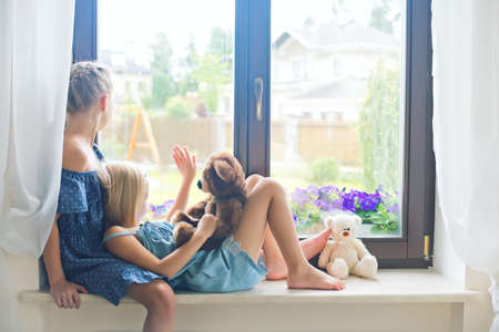 Two cute european toddler girls sitting on sill near window at home playing teddy bears happy and funny. Colorful back yard at background Stock Photo