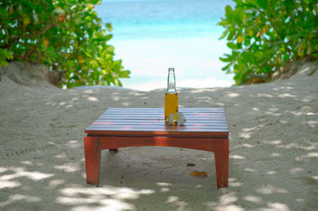 Glass bottle of refreshing bewerage on the table with ocean view on background