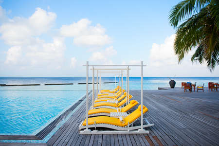 Yellow sunbeds near the swimming pool on tropical luxury island resort