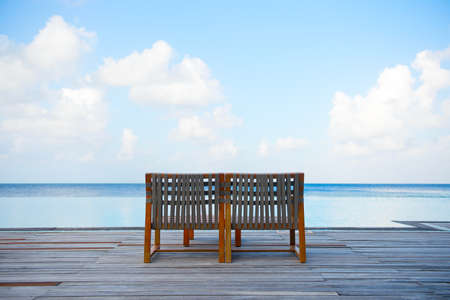 Lonely armchair for two near swimming pool with view on turquoise ocean