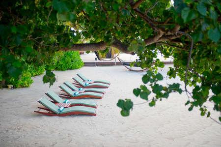 Sunbeds on the sand seashore on luxury tropical island resort Stock Photo