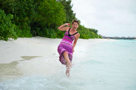Happy young woman wearing long dress having fun in waves of turquoise ocean and laughing