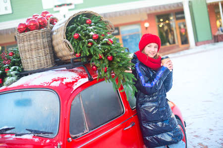 Happy young model girl with cup of hot beverage in hands stand near decorated red car ready for shoping in europe outlet. Strape on her coat