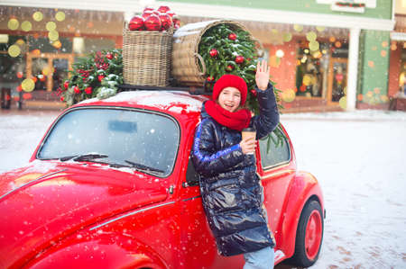 Happy young model girl with hot beverage in hands waves to someone comming. Girl stay near fashion red car ready for shoping in europe outlet. Strape on her coat