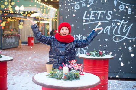 Hally european teenage girl laugh and drop snowflakes in air. Model is on christmas fair